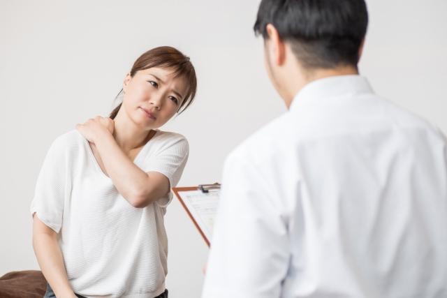 肩こりの悩みを整骨院で相談する女性