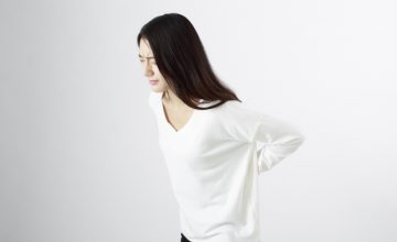長引く腰痛に悩む女性