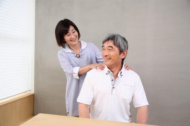 夫の肩をマッサージしてあげる妻