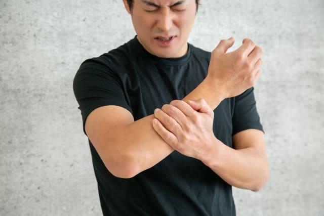 肘に痛みを感じている男性